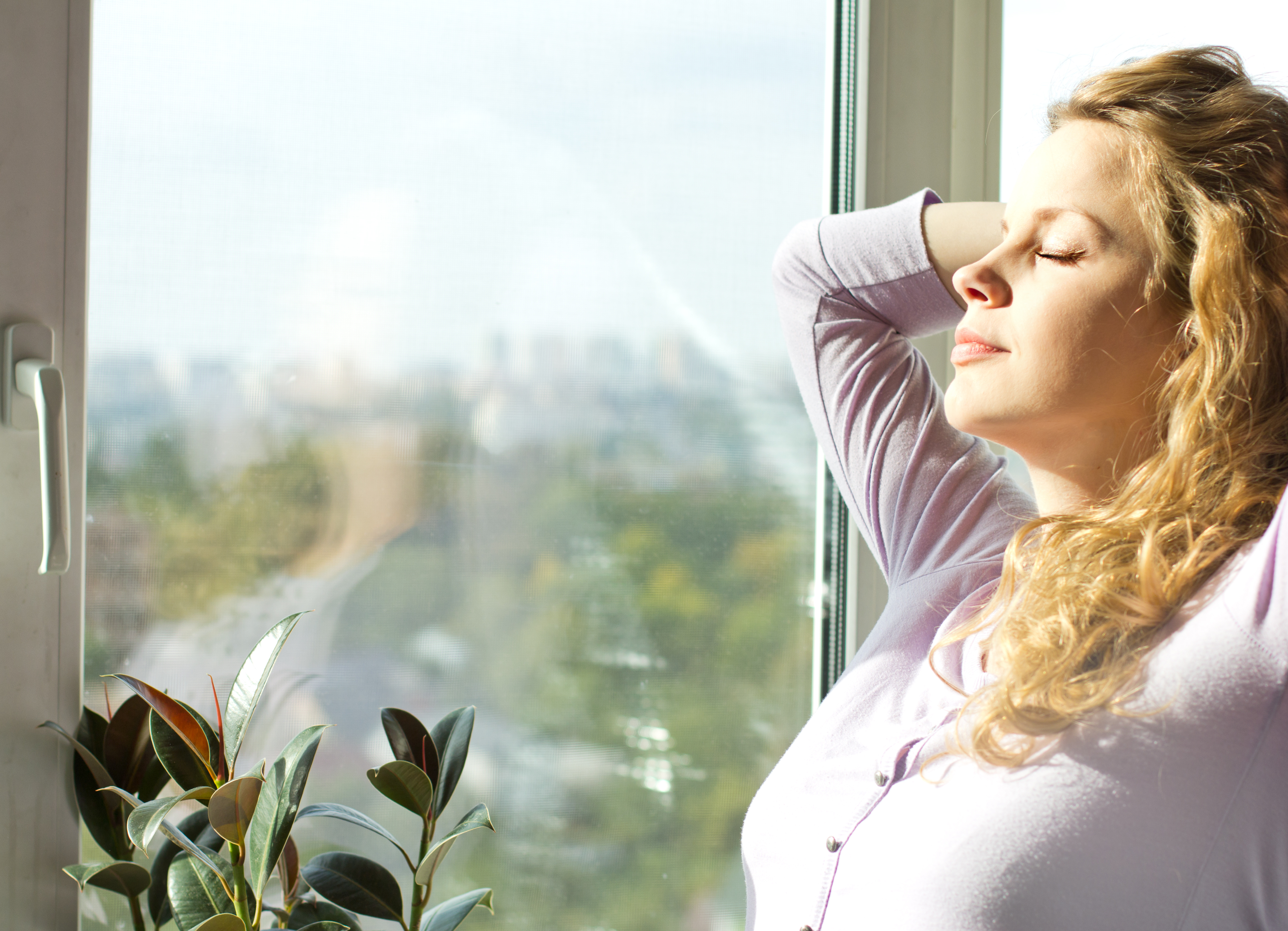 pregnant blonde standing near the window and enjoy the sun.