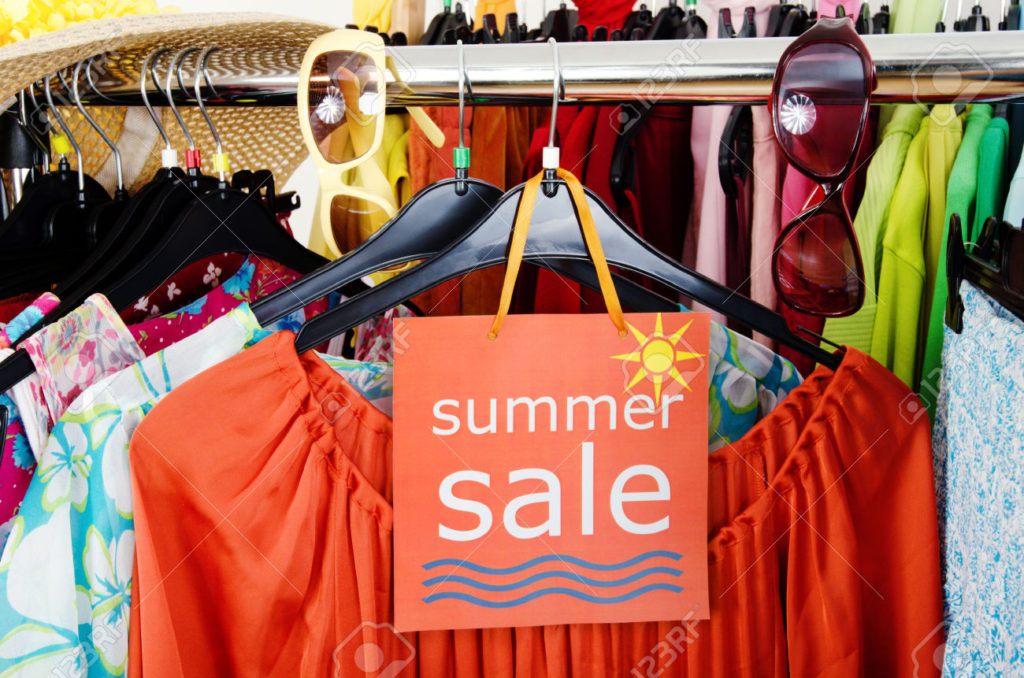 29455470-close-up-on-a-big-sale-sign-for-summer-clothes-clearance-rack-with-colorful-summer-outfits-and-acces-stock-photo